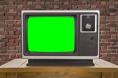 Televisión vieja y pantalla y pared de ladrillo verdes dominantes de la croma Foto de archivo