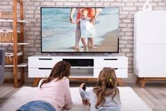Televisi?n de observaci?n de la madre y de la hija fotografía de archivo libre de regalías