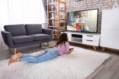 Televisi?n de observaci?n de la mujer joven en casa fotografía de archivo libre de regalías