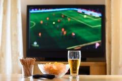 Televisie, TV die (voetbal, voetbalgelijke) letten op met snackslyi royalty-vrije stock foto's