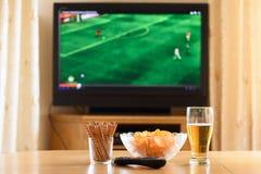 Televisie, TV die (voetbal, voetbalgelijke) letten op met snackslyi stock fotografie