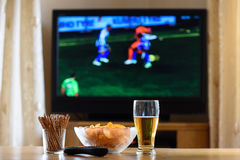 Televisie, TV die (voetbal, voetbalgelijke) letten op met snackslyi royalty-vrije stock afbeelding