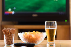 Televisie, TV die (voetbal, voetbalgelijke) letten op met snackslyi stock foto