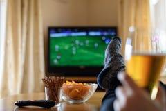 Televisie, TV die (voetbalwedstrijd) letten op met voeten op lijst en Stock Afbeelding