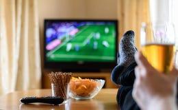 Televisie, TV die (voetbalwedstrijd) letten op met voeten op lijst en Stock Afbeeldingen
