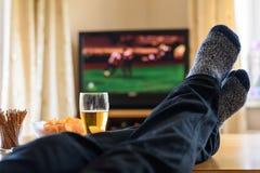 Televisie, TV die (voetbalwedstrijd) letten op met voeten op lijst en royalty-vrije stock foto