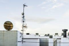 Televisieantenne en satellietschotel op wit dak, Hemelbackgro stock foto's