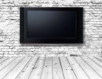 Televisietoestel op een oude muur stock foto's