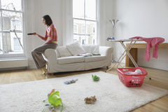 Televisión de observación de la mujer en sala de estar Fotos de archivo