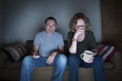 Televisión de observación de los pares que ríe y desconcertada Fotos de archivo libres de regalías