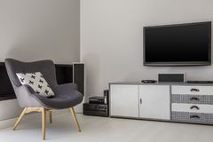 Television above cabinet next to grey armchair with patterned pi. Llow in flat interior. Real photo concept stock image