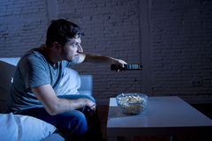 Television addict man sitting on home sofa watching TV eating popcorn using remote control. Young happy television addict man sitting on home sofa watching TV Royalty Free Stock Image