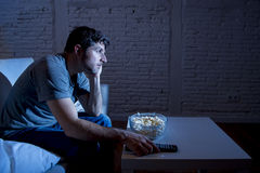 Television addict man sitting on sofa watching TV eating popcorn using remote control looking bored. Young television addict man sitting on home sofa watching TV Stock Images