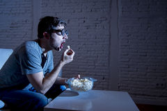 Television addict man on sofa watching TV and eating popcorn in funny nerd geek glasses Royalty Free Stock Photo