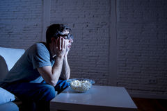 Television addict man on sofa watching TV and eating popcorn in funny nerd geek glasses Stock Photo