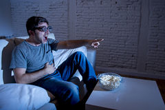Television addict man on sofa watching TV in funny nerd geek glasses laughing crazy Stock Photos