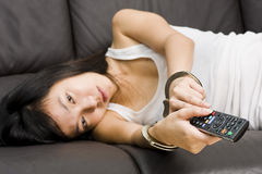 Television addiction with remote cuffed to hands Stock Photo