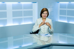 Television anchorwoman at TV studio. Smiling television anchorwoman at studio arranging microphone stock image