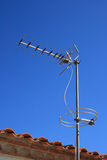 Television antenna. On a tiled roof over blue sky Stock Photo