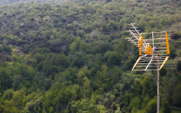 Television antenna ready to receive signals. With a forest in the background Stock Photos