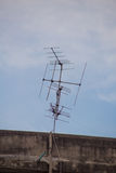 Television antenna. Television antenna on roof of old building with blue sky Royalty Free Stock Photography