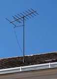 Television antenna on the roof over blue sky Stock Photography