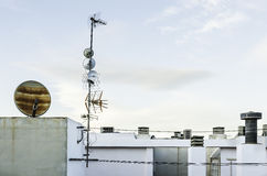 Television antenna and satelite dish on white roof , Sky backgro Stock Photos