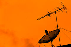 Television antenna and satellite dish on the roof with sunset sk Stock Photos