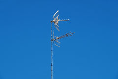 Television antenna set against a blue sky. Royalty Free Stock Image