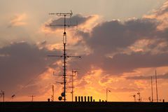 Television antennas on the roof pictured at sunset stock photos