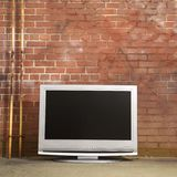 Television by brick wall. Stock Photo