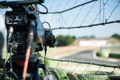 Television camera handle detail on motor sport circuit. Television camera on motor sport circuit, selective focus detail on handle and track out of focus in stock image