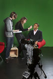 Television camera on tripod in studio with crew in Stock Photo