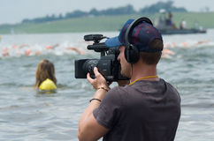 Television cameraman videos the Midmar Mile swimming event Stock Image