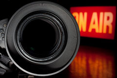 Television Film Camera. With focus on the rim of the lens. On Air Broadcast sign in the background stock photography