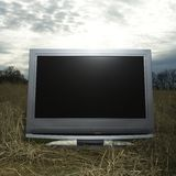 Television in grassy field. Stock Photos