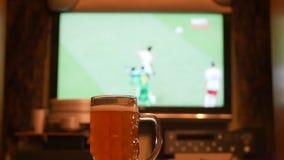 Television hållande ögonen på fotboll för TV, fotbollsmatch med öl på tabellen arkivfilmer