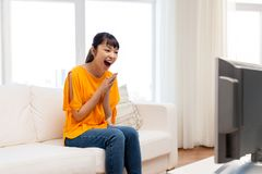 Happy asian woman with watching tv at home. Television, leisure and people concept - happy smiling asian woman watching tv at home and having fun Stock Image