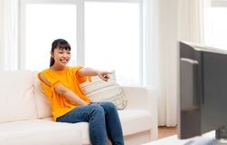 Happy asian woman with watching tv at home. Television, leisure and people concept - happy smiling asian woman watching tv at home and having fun Royalty Free Stock Photo