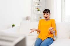 Happy asian woman with watching tv at home. Television, leisure and people concept - happy smiling asian woman watching tv at home and having fun Royalty Free Stock Image