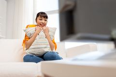 Happy asian woman with watching tv at home. Television, leisure and people concept - happy smiling asian woman watching tv at home and having fun Royalty Free Stock Photography