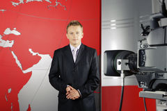 Television news reporter and video camera. Serious middle age attractive news reporter standing in front of the video camera in a television studio Stock Image