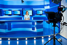 Television newscaster at blue TV studio. Television announcer at studio during live broadcasting Royalty Free Stock Photography