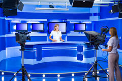 Television newscaster and teleoperator at TV studio. Television announcer at studio during live broadcasting Royalty Free Stock Image