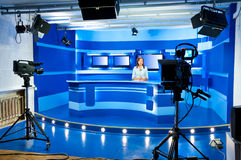 Television newscaster at TV studio. A television announcer at studio during live broadcasting Royalty Free Stock Photos