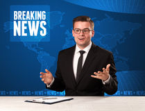 Television presenter in front telling breaking news with blue mo Stock Photo