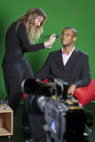 Television presenter and make-up artist on TV set. A make-up artist adds final touches to a presenter on a television set with a TV camera out of focus in the Stock Photo