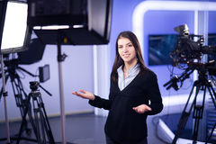 Television presenter recording in news studio.Female journalist anchor presenting business report,recording in television studio. News camera,light equipment Royalty Free Stock Photography