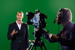Presenter in studio with TV camera and Camera Oper Stock Images