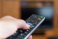 TV Remote controller in hand Stock Photo
